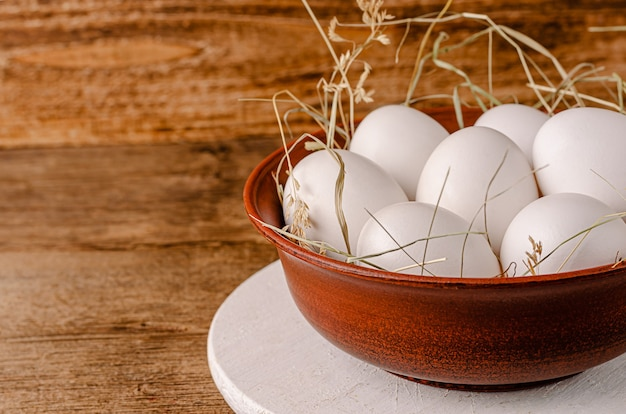 White chicken eggs in bowl on rustic wooden table