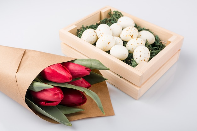 White chicken eggs in box with tulips bouquet