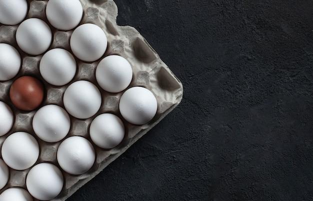 White chicken eggs in a cardboard box on dark concrete background.