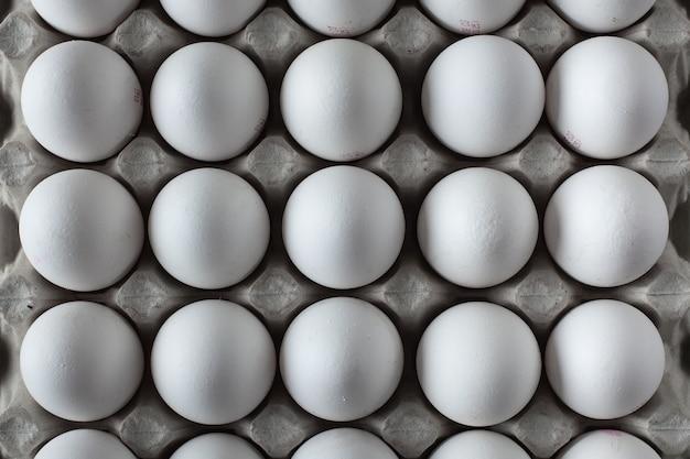 White chicken eggs in a cardboard box.