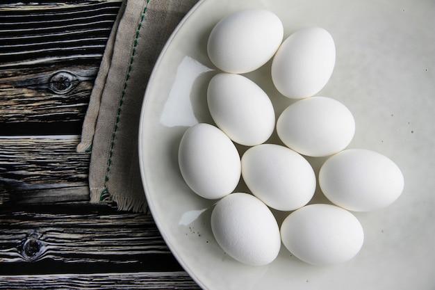 White chicken eggs in a dark plate on a brown wooden background