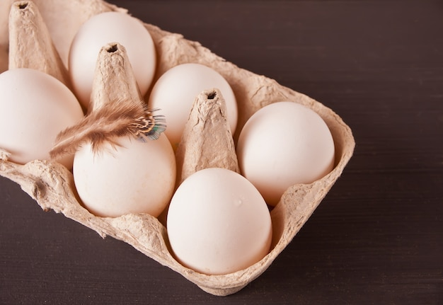 White chicken eggs in egg paper tray with feather on the black background