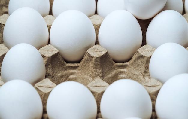 Белые куриные яйца в контейнере