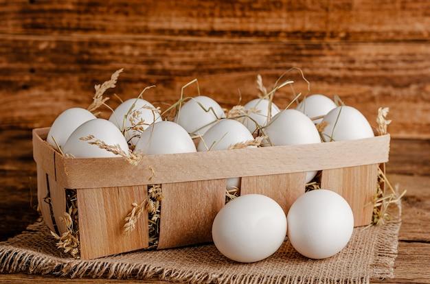 건초와 함께 나무 용기에 흰색 닭고기 달걀. 공간을 복사합니다.