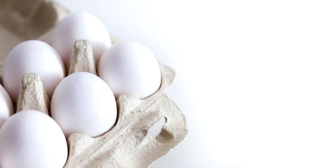 白い孤立した背景のパッケージで白い鶏卵。箱に入った卵、自然な健康食品。クリエイティブなミニマルな背景。有機農業の概念。碑文またはロゴの場所