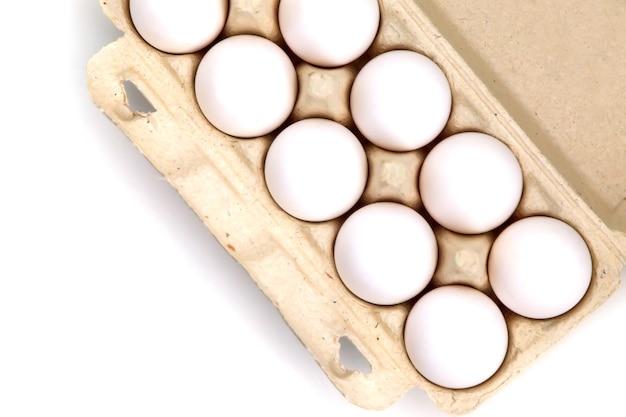 白い孤立した背景のパッケージで白い鶏卵。箱に入った卵、自然な健康食品。クリエイティブなミニマルな背景。有機農業の概念。碑文やロゴの場所