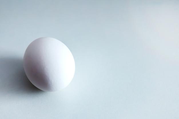 Белые куриные яйца на белом фоне. яйцо на столе, натуральная здоровая пища. творческий минималистичный фон. концепция органического земледелия и правильного питания. место для надписи или логотипа