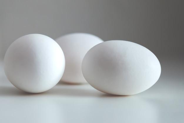흰색 바탕에 흰색 닭고기 달걀입니다. 식탁 위의 계란, 천연 건강 식품. 크리에이 티브 최소한의 배경입니다. 개념 유기농업과 적절한 영양. 비문 또는 로고를 위한 장소
