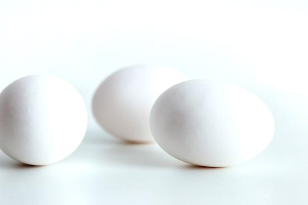 Белые куриные яйца на белом фоне изолированных. яйцо на столе, натуральная здоровая пища. творческий минималистичный фон. концепция органического земледелия и правильного питания. место для надписи или логотипа