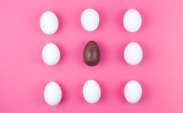 White chicken eggs with chocolate egg on table