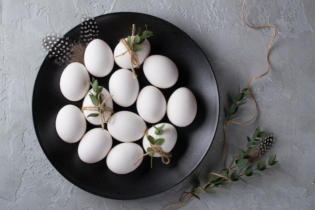 White chicken raw  eggs on a black plate. top view and copy space. easter  photo concept.