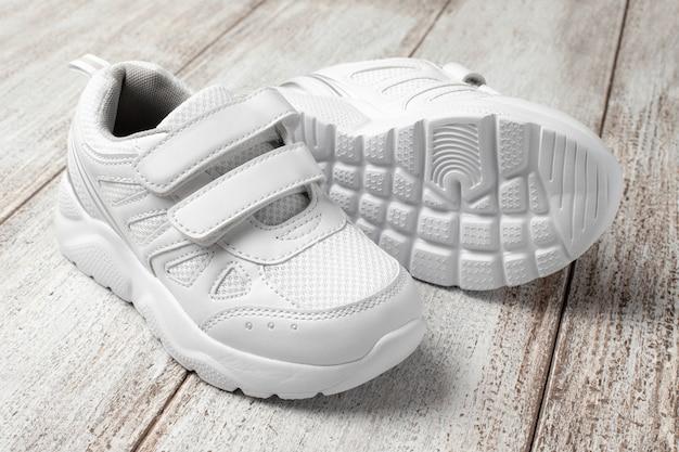 Белые детские кроссовки на светлом фоне пара модных спортивных кроссовок с застежкой на липучке ...