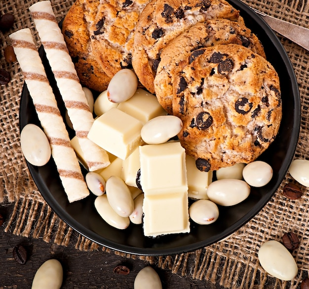 White chocolate, almonds and cookies on a wooden surface
