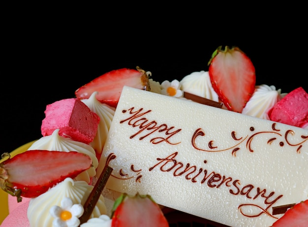 White chocolate anniversary edible greeting card on the top of strawberry jelly vanilla mousse cake