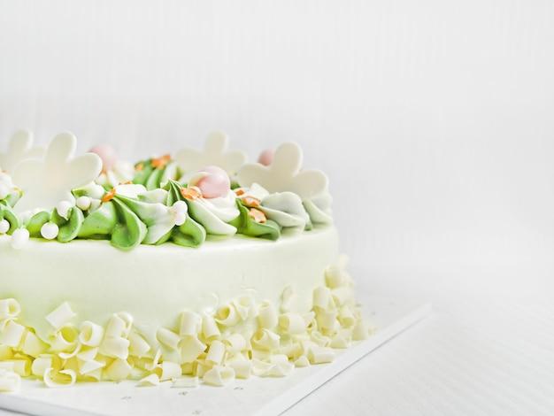 ホワイトチョコレートの誕生日ケーキ。クリーミーで、白と緑で、美しい螺旋状の花びらがあります。白い布の背景に
