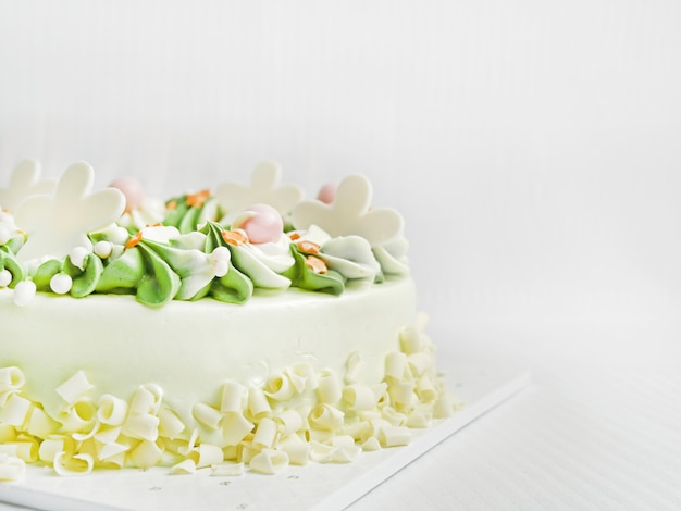 White chocolate birthday cake. is creamy, white and green, with beautiful spiral petals. on a white fabric background