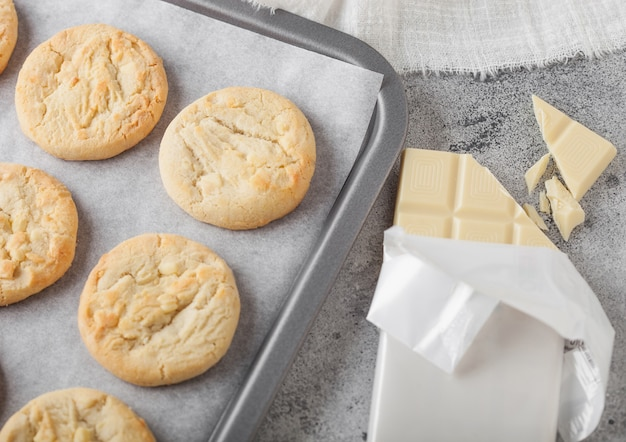 White chocolate biscuit cookies on baking tray on light kitchen table background with white chocolate bar. top view