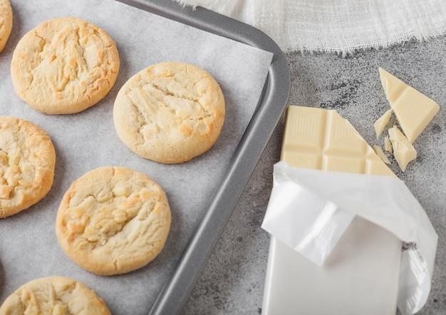 ホワイトチョコレートバーと明るいキッチンテーブルの背景のベーキングトレイにホワイトチョコレートビスケットクッキー。上面図