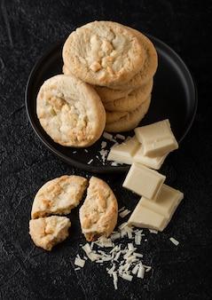 チョコレートブロックと暗いテーブルのカールと黒のセラミックプレートにホワイトチョコレートビスケットクッキー。