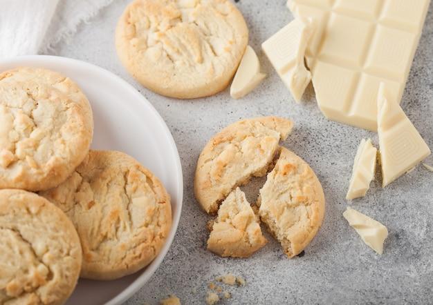 ライトテーブルの背景にチョコレートブロックとカールが付いた白いセラミックプレート上のホワイトチョコレートビスケットクッキー。上面図
