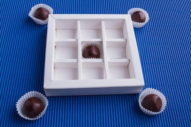 Коробка белого шоколада с коричневыми конфетами на синем фоне