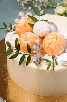 青い背景にみかんで飾られたホワイトチョコレートケーキ。垂直フレーム。閉じる