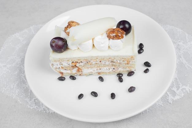 Белый шоколадный торт на белой тарелке. фото высокого качества