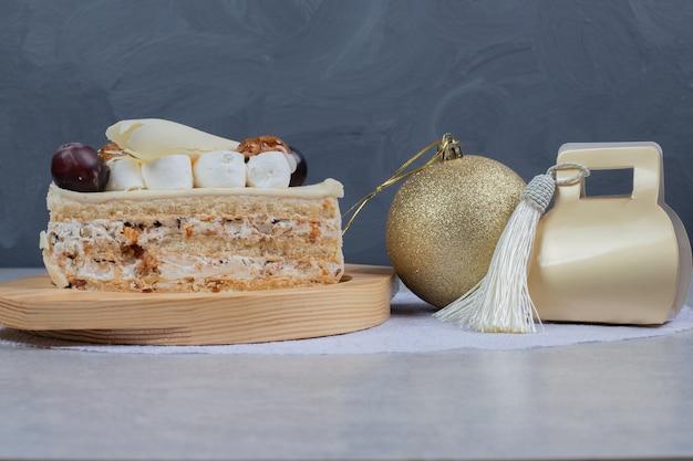 Белый шоколадный торт на деревянной тарелке с рождественским подарком и мячом. фото высокого качества