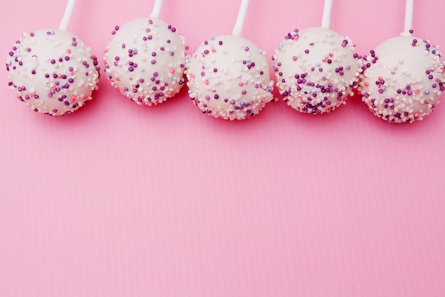White chocolate cake pops with powder on a pink background with copyspace
