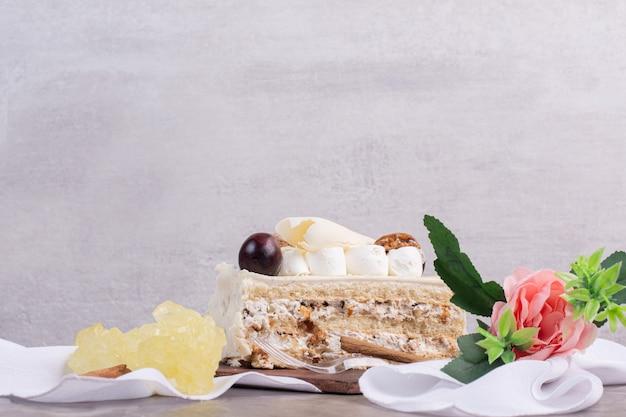 大理石のテーブルにキャンディーと花のホワイトチョコレートケーキ。