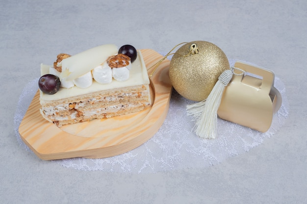 White chocolate cake on wooden plate with christmas gift and ball. high quality photo