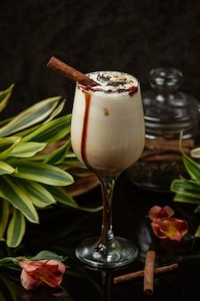 휘핑 크림과 계피 스틱이 든 유리에 화이트 초콜릿 커피