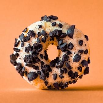 Пончик из белого шоколада с черным печеньем на оранжевом фоне