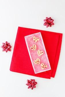 Сердечки из белого шоколада с клубникой в подарочной коробке на красной салфетке