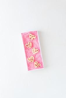Сердечки из белого шоколада с клубникой в подарочной коробке на белом