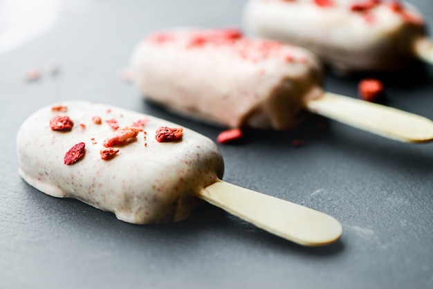 Леденцы мороженого из белого шоколада на черном камне
