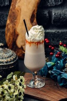 Мокко из белого шоколада в стакане со взбитыми сливками и соломой