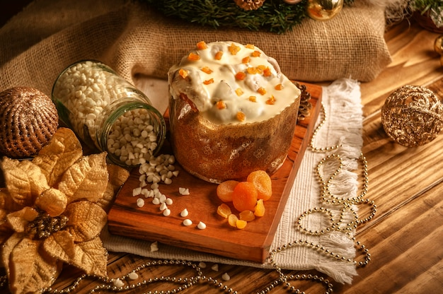 クリスマスの装飾品と木製のテーブルにドライアプリコットとホワイトチョコレートのパネットーネ