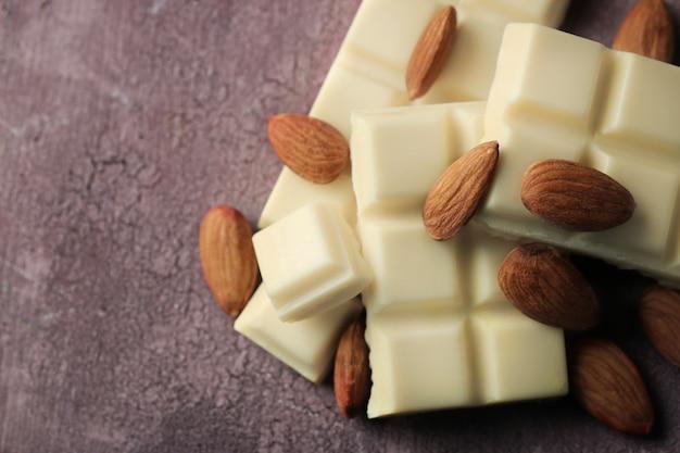 カラーの木製の背景にナッツとホワイトチョコレートの部分