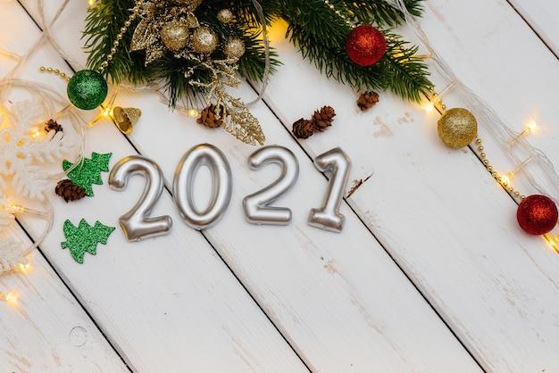 Белый новогодний фон украшен праздничным декором, фонарями, снежинками и ветками елки