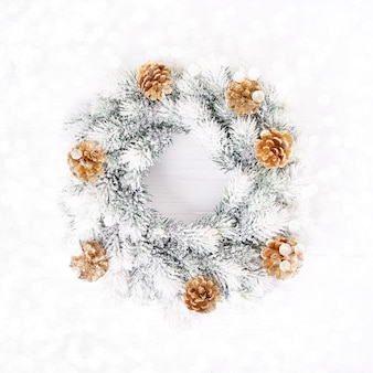 White Christmas background. White Christmas wreath with gold cones on white background. Copy space