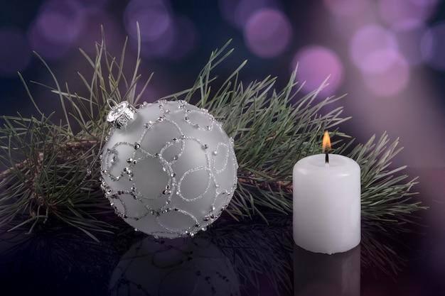 Белый елочный шар и белая свеча с еловой веточкой на фоне фиолетовых бликов размыты