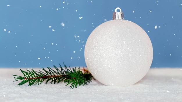 Белый елочный шар и ветка елки во время снегопада