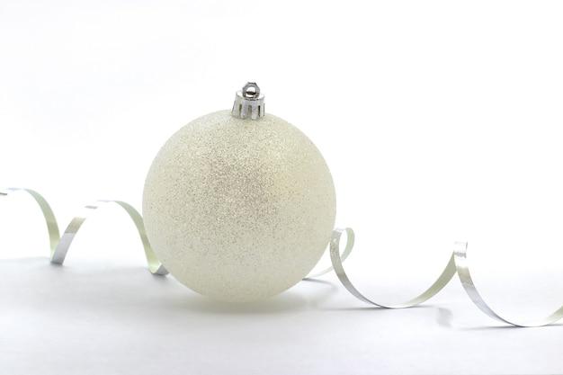 Белый елочный шар и серпантин