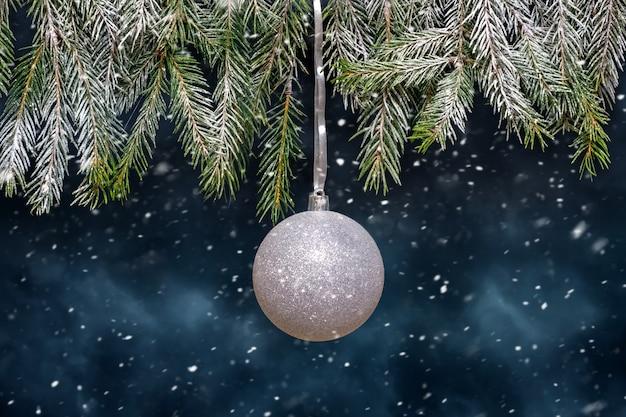 Белый елочный шар на елке во время снегопада