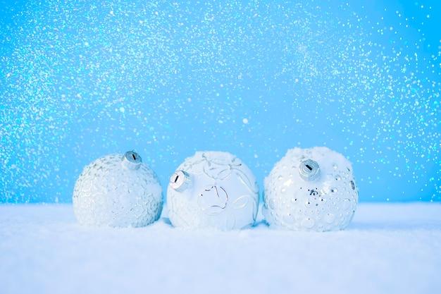 Белые елочные шары на белом снегу
