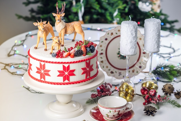 White christmas cake with red ornament on top decorated with mastic figures deer and fresh berries on a festive table