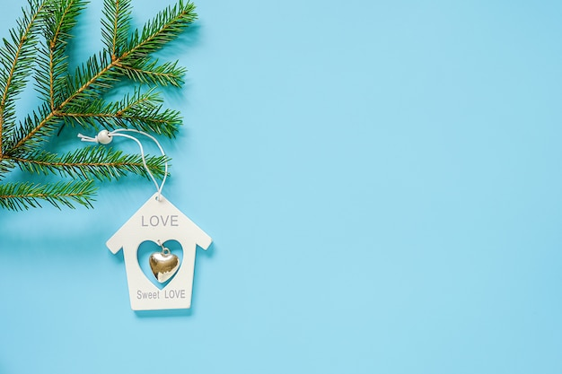 White christmas decoration toy house on fir branch on blue background. concept merry christmas or happy new year.