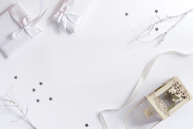 White christmas flat lay with gift boxes old-fashioned candle lantern and  confetti decoration