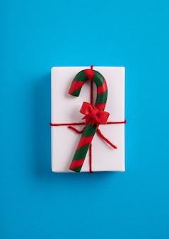 Scatola regalo natalizia bianca decorata con un bastoncino di zucchero sulla superficie blu